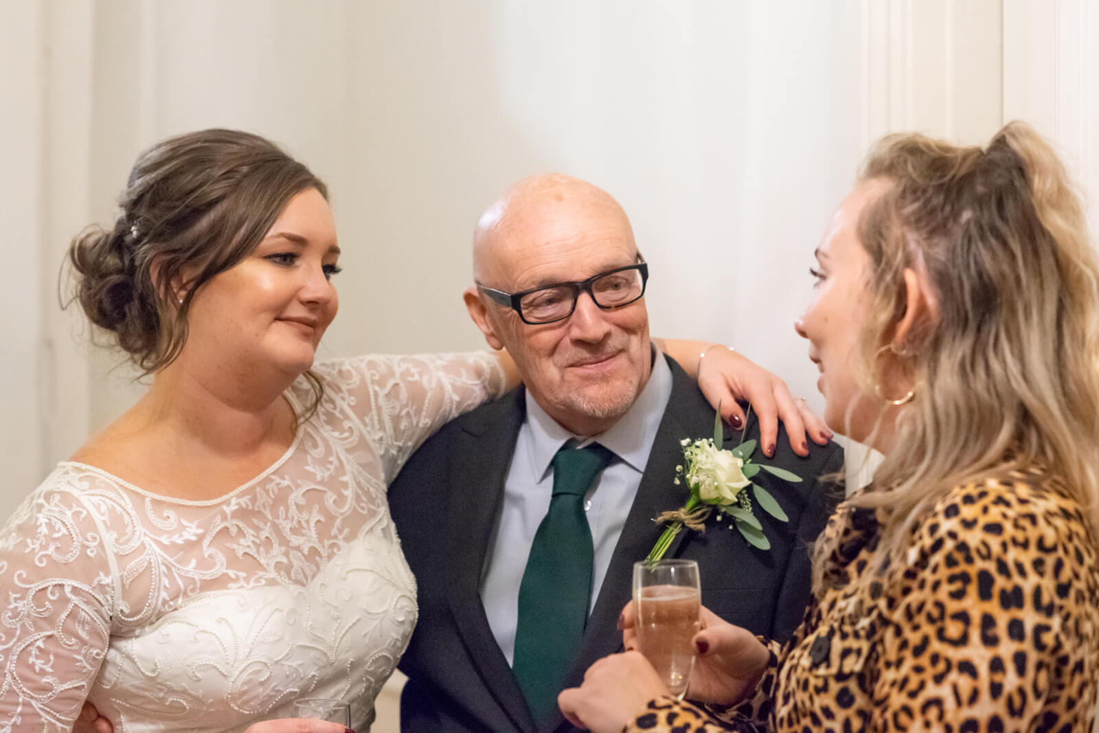 Bride with her arm around her father's shoulders talks to a friend