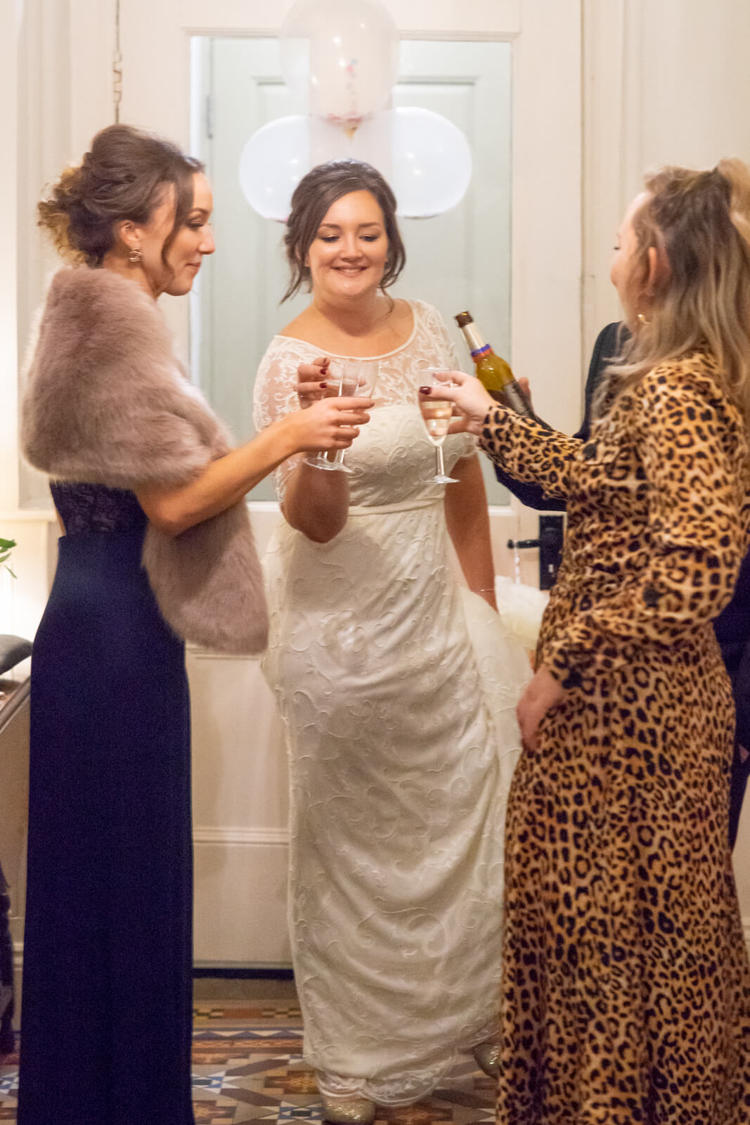 Bride and her friends clink glasses and toast whilst standing in a tiled hallway