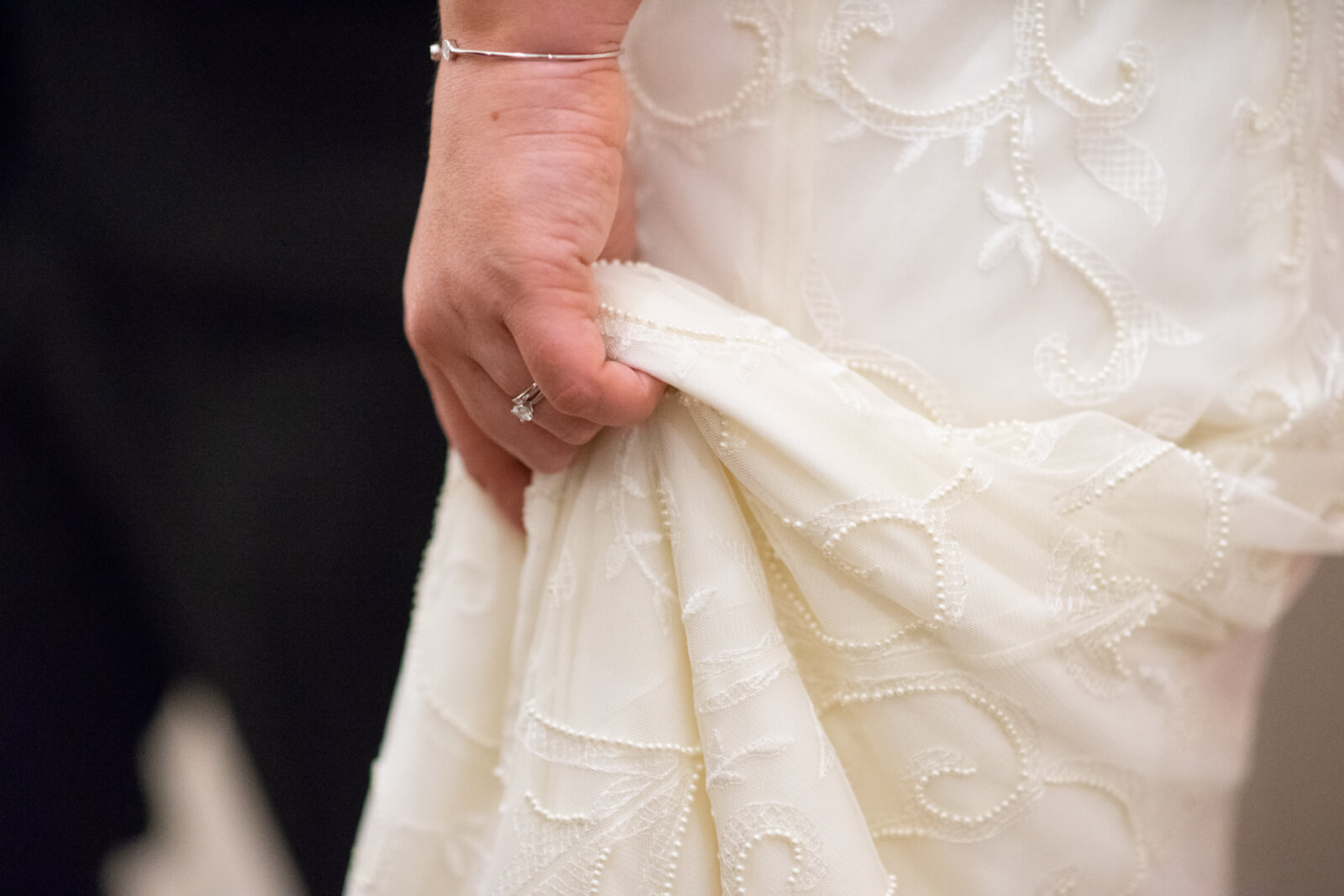 Close up of the bride's hand holding up her dress and wearing her new wedding ring