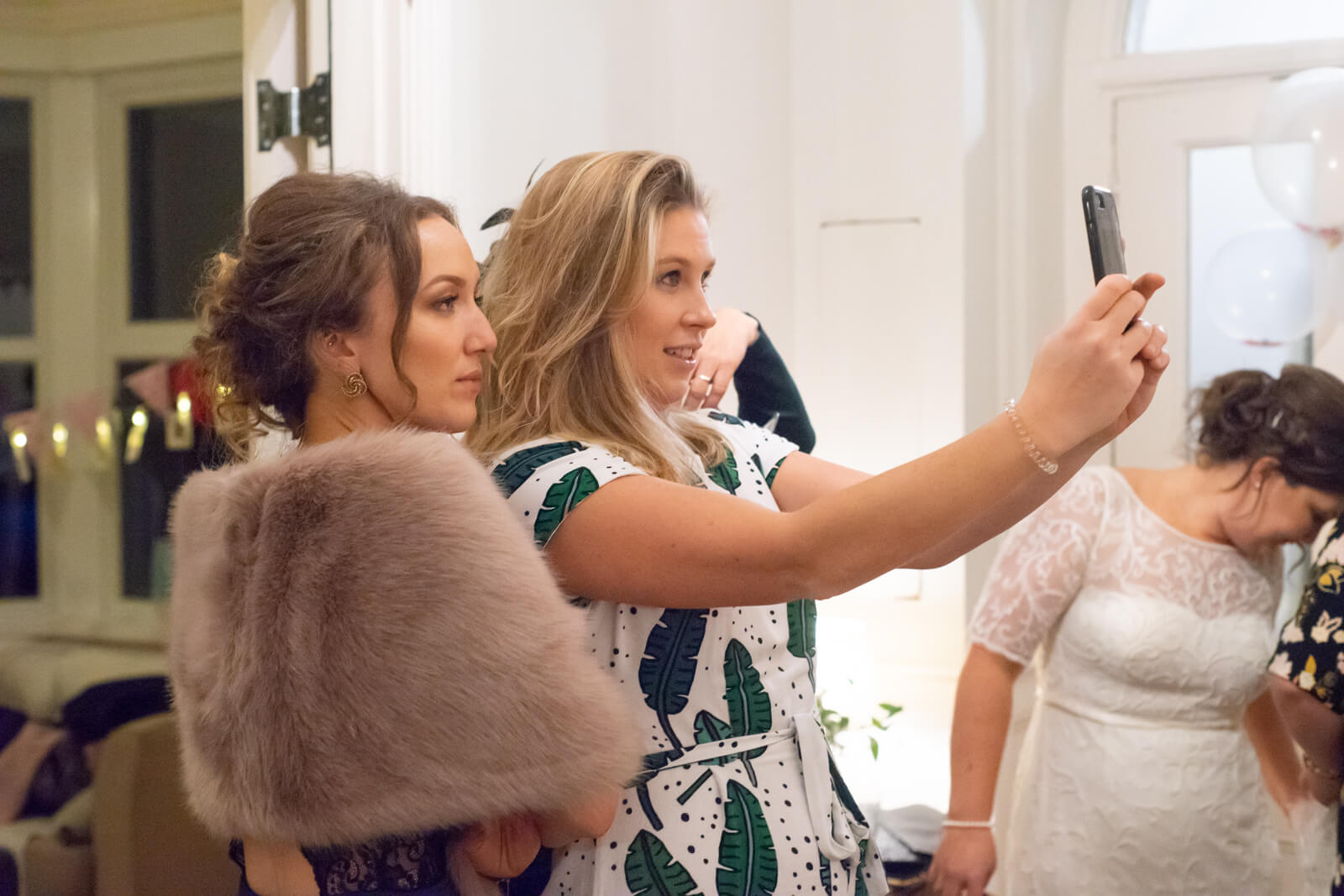 Female guests at the wedding reception take a group selfie