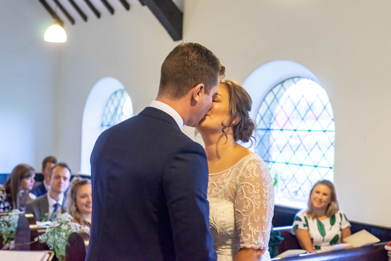 Bride and groom kiss in their small chapel wedding