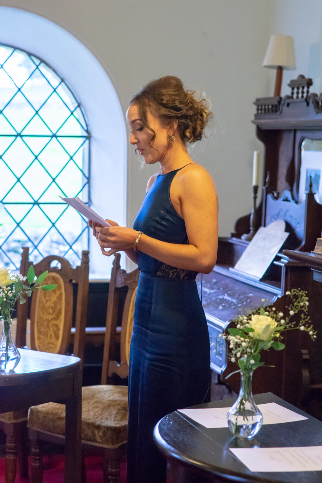 Bridesmaid in a blue dress gives a reading during the ceremony