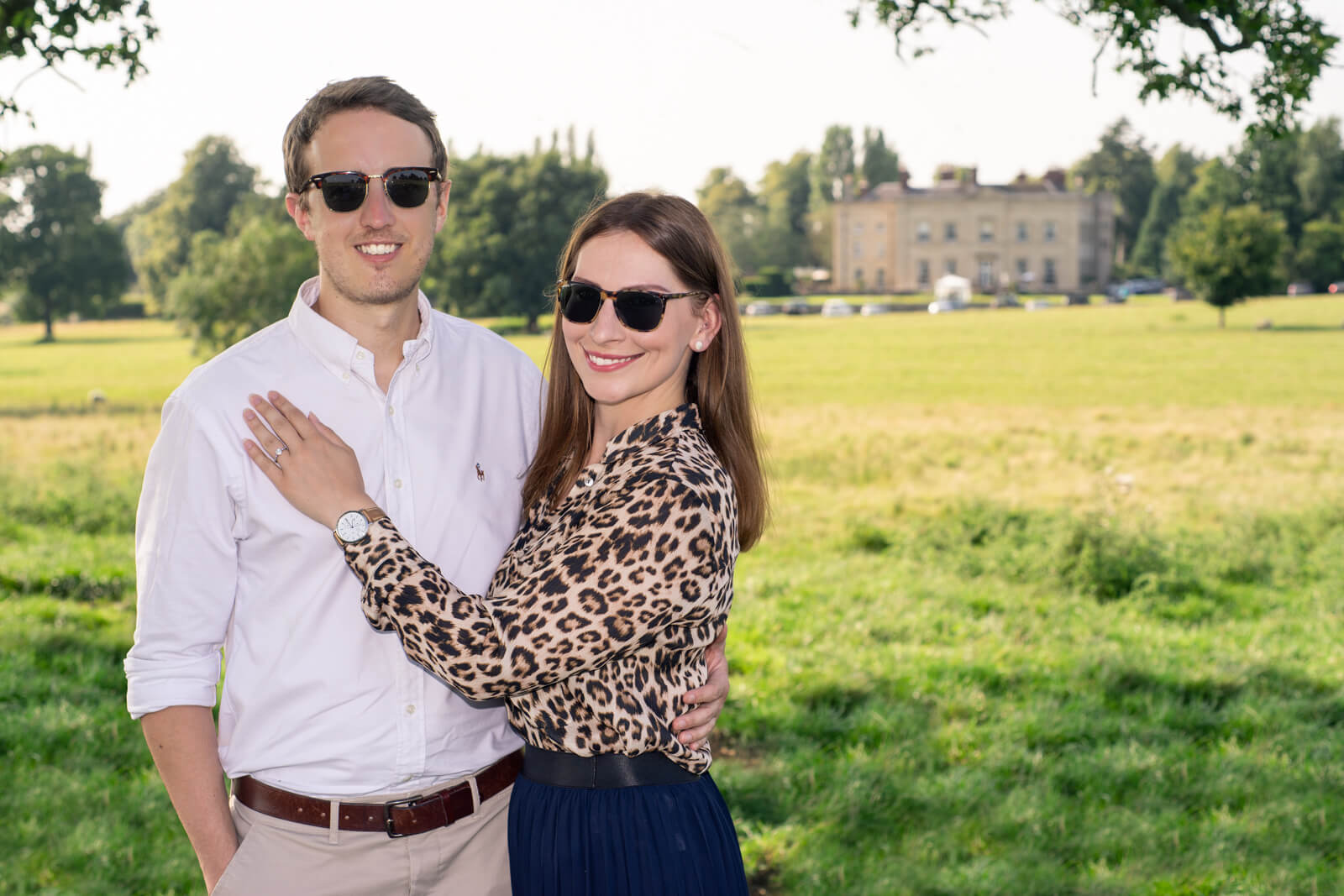 Engaged couple standing in front of a country estate in sunglasses