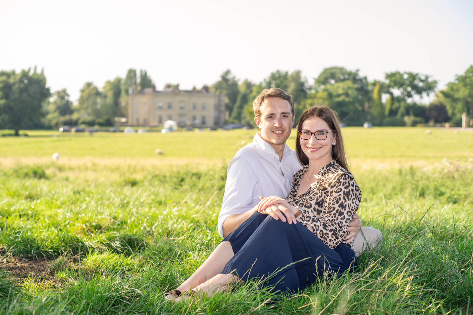 Engaged couple sit together in a grass field with a manor house in the background