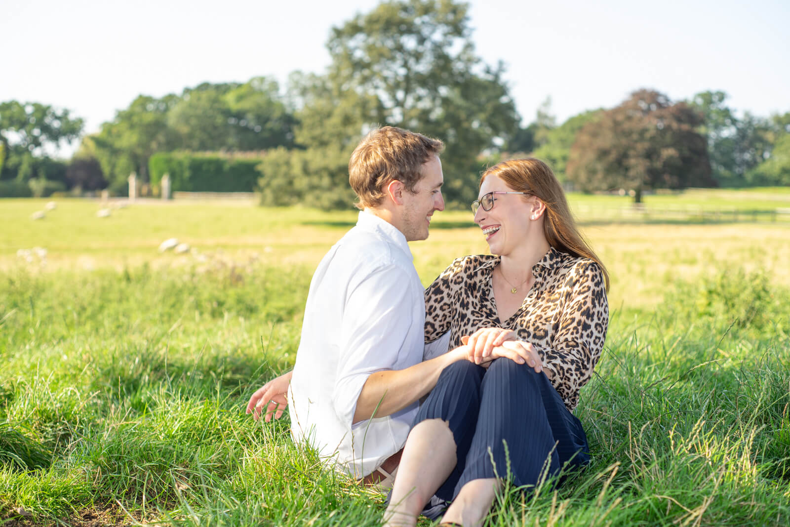 Young couple sit together on the grass laughing in the sunshine