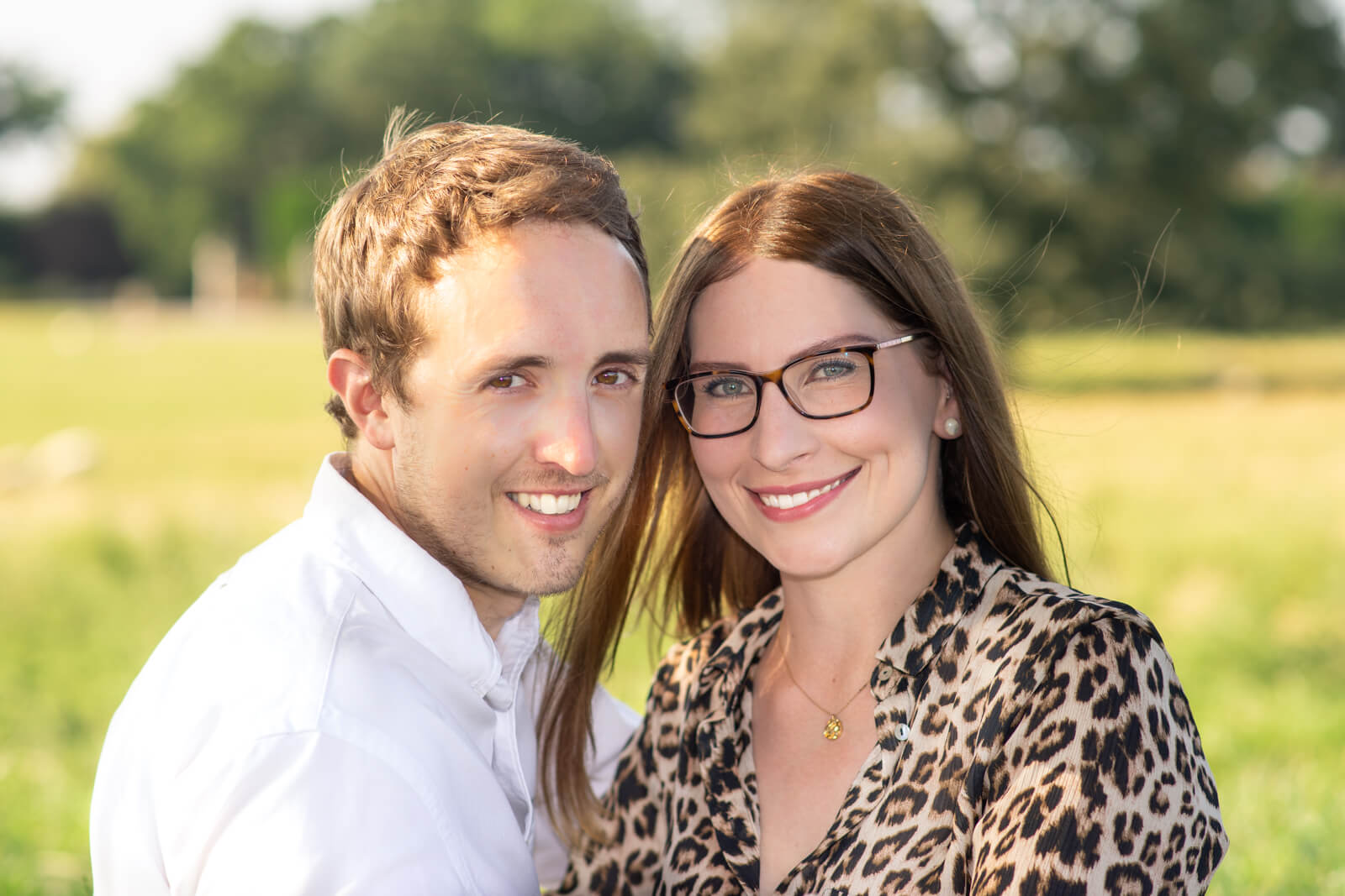 Engagement photo of a couple looking at the camera with green grass in the background