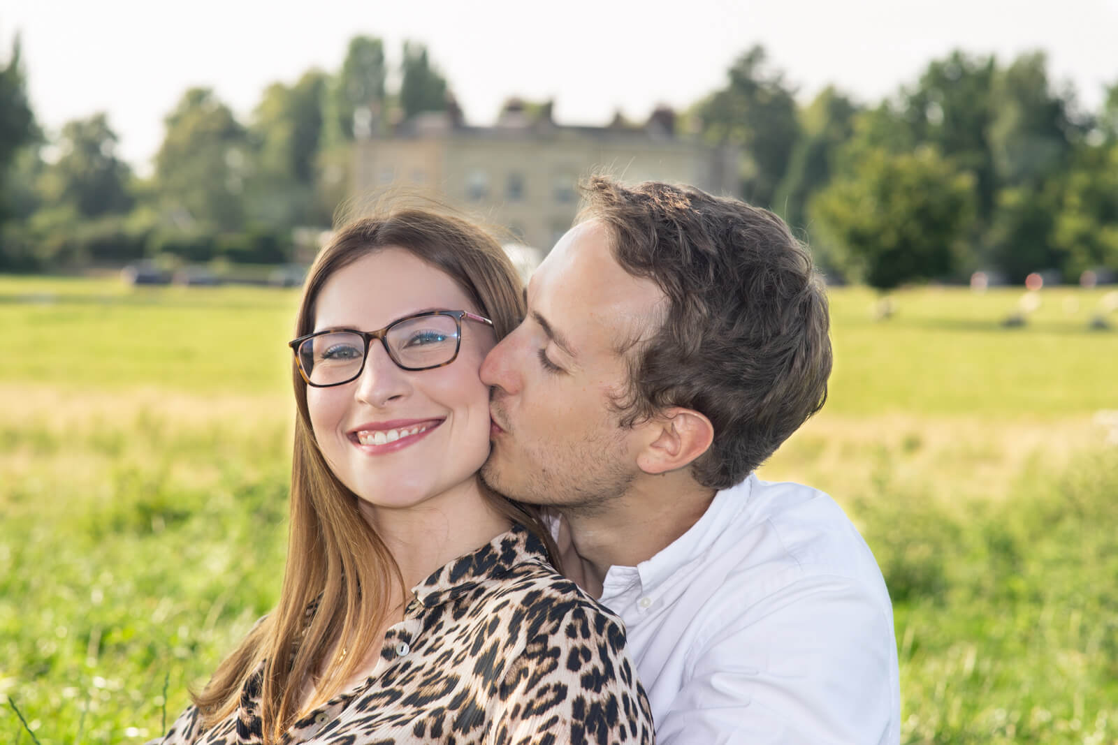 Man kisses his fiance on the cheek as she smiles at the camera