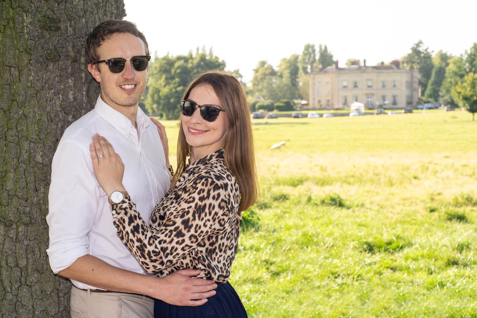 Couple in sunglasses lean against tree on a sunny day