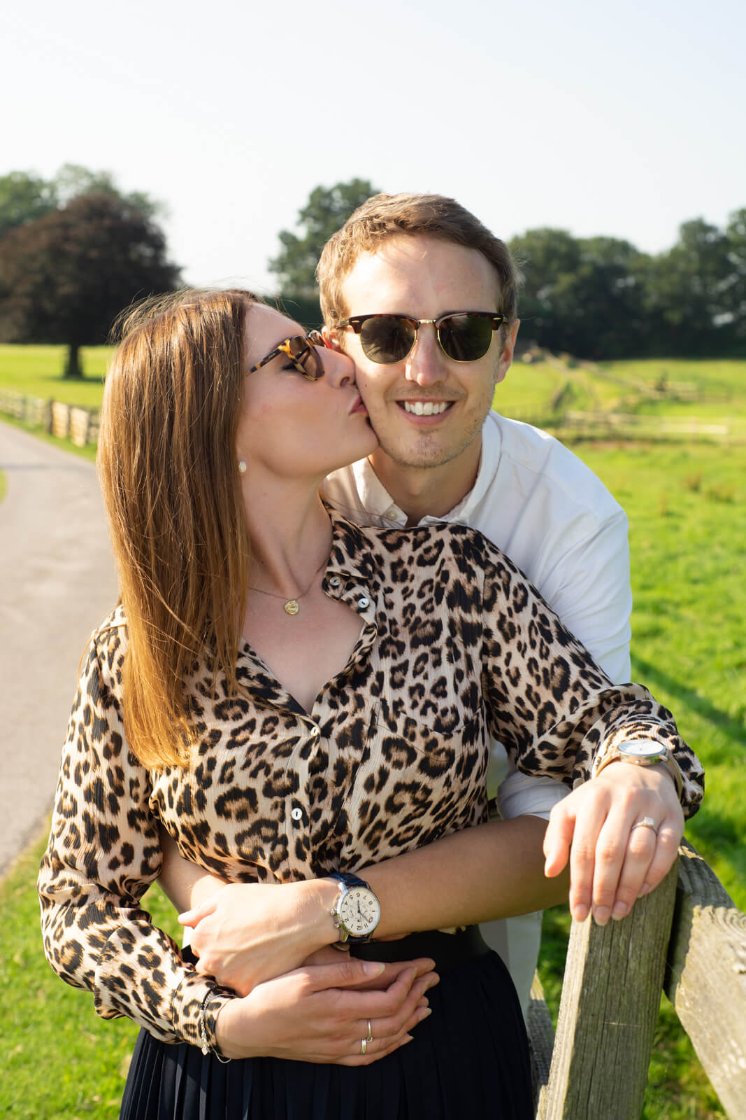 Young woman in leopard print leans back and kisses her fiance on the cheek