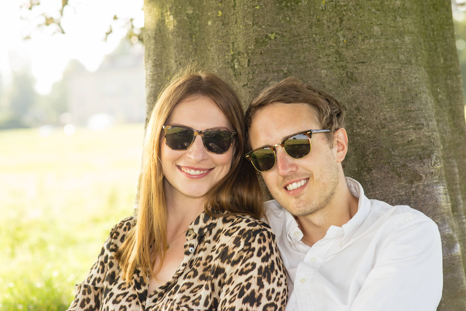Engaged couple wearing sunglasses look at the camera on a bright hot day