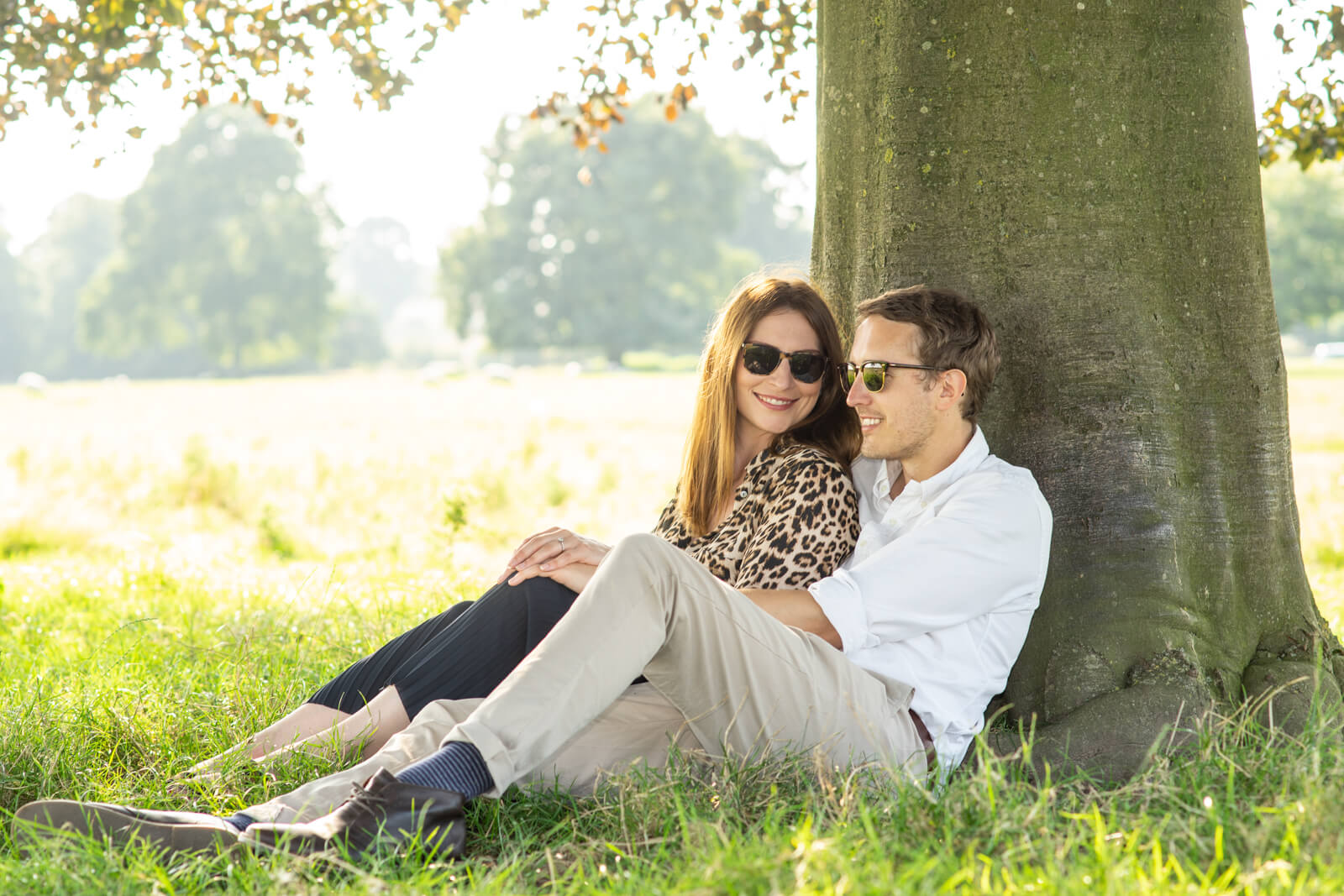 Young couple sit together under a tree on a summers day