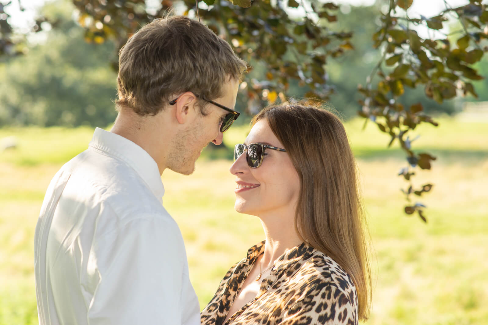 Couple in sunglasses face each other whlst standing in the shade of a tree