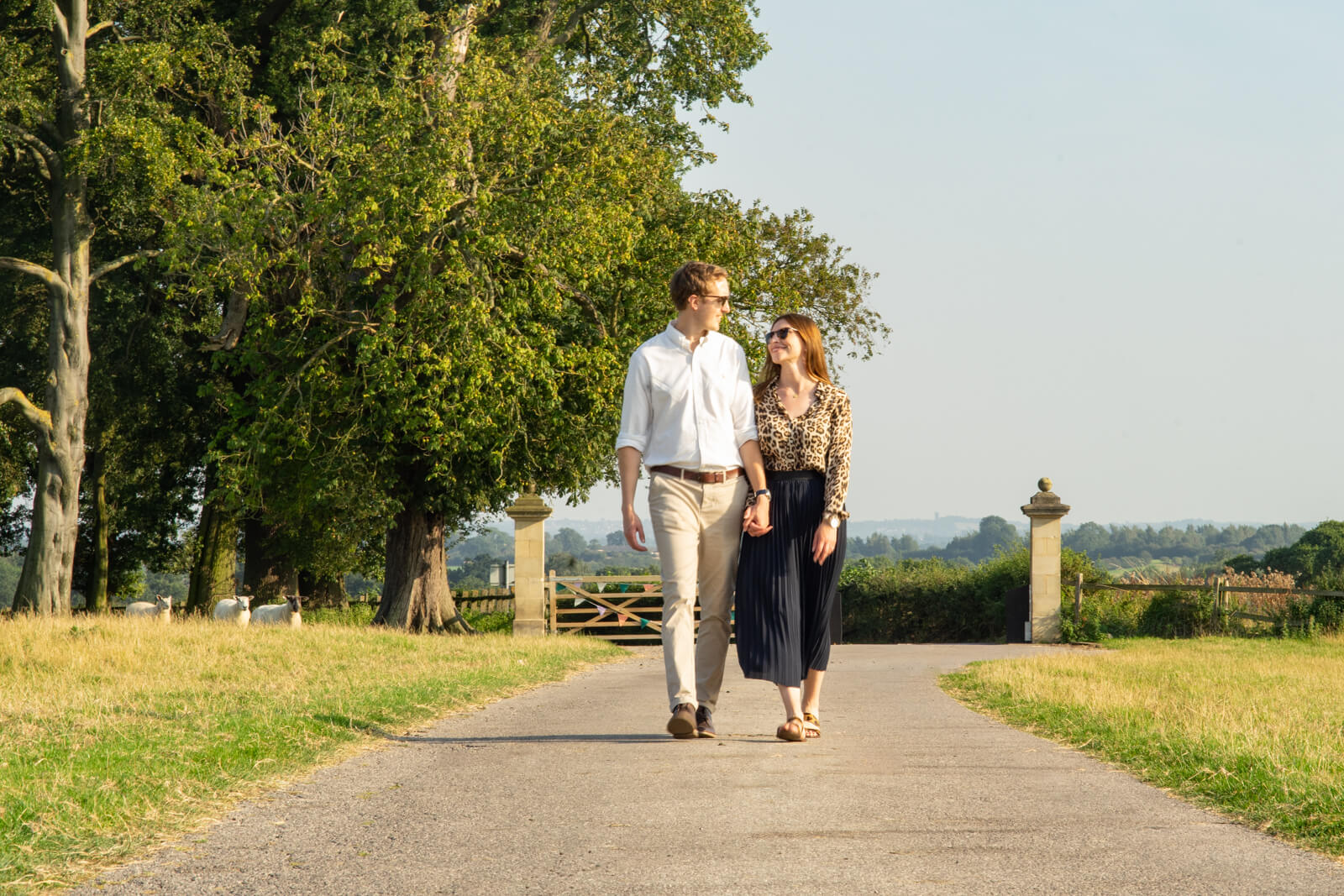 Engaged couple walk hand in hand down a country estate drive