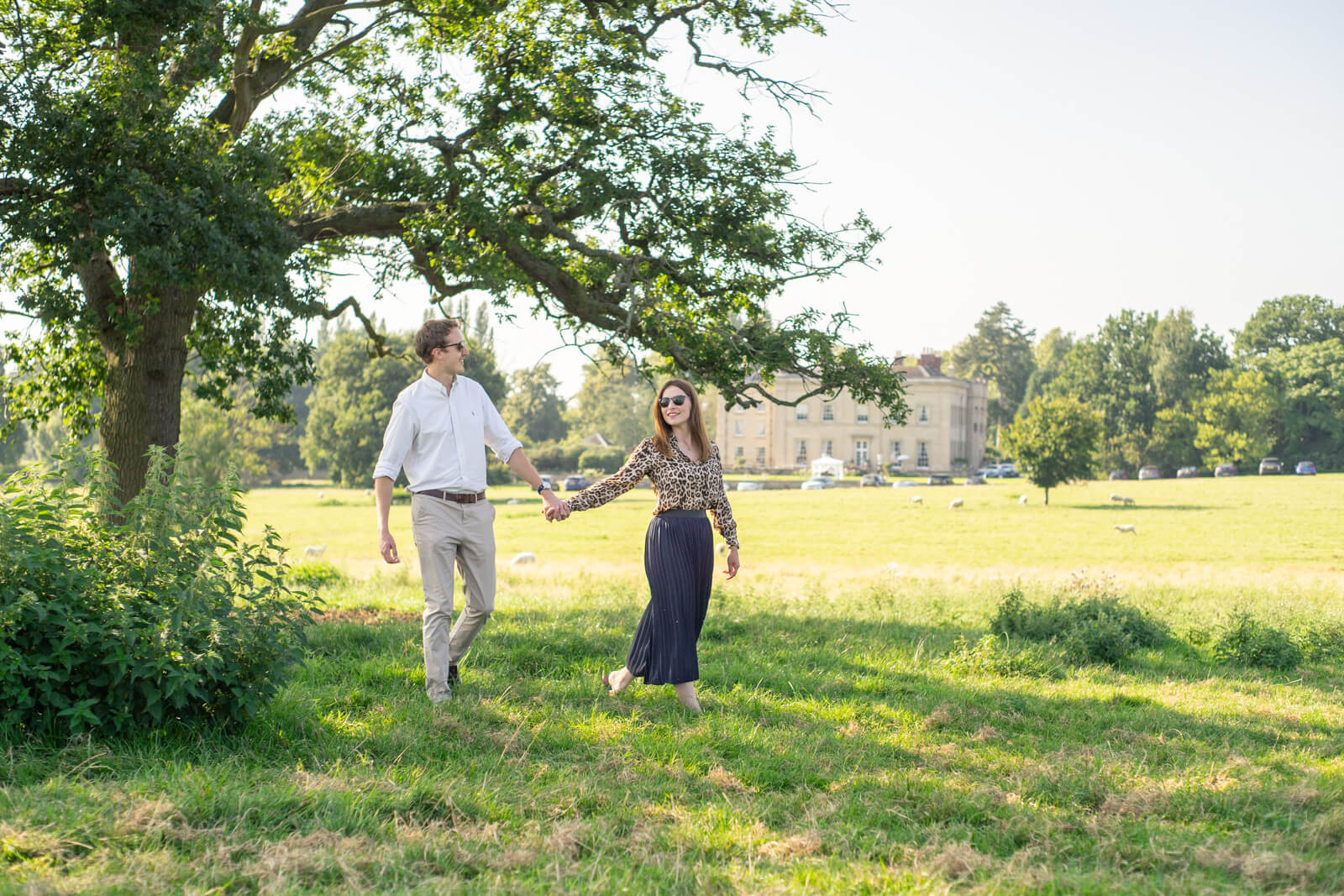 Couple hold hands and walk under a tree on a sunny day