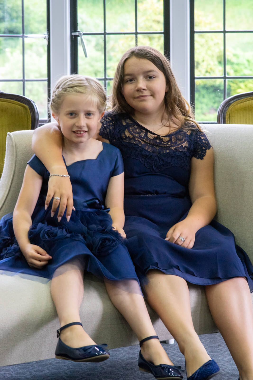 Young bridesmaids in blue with their arms around each other