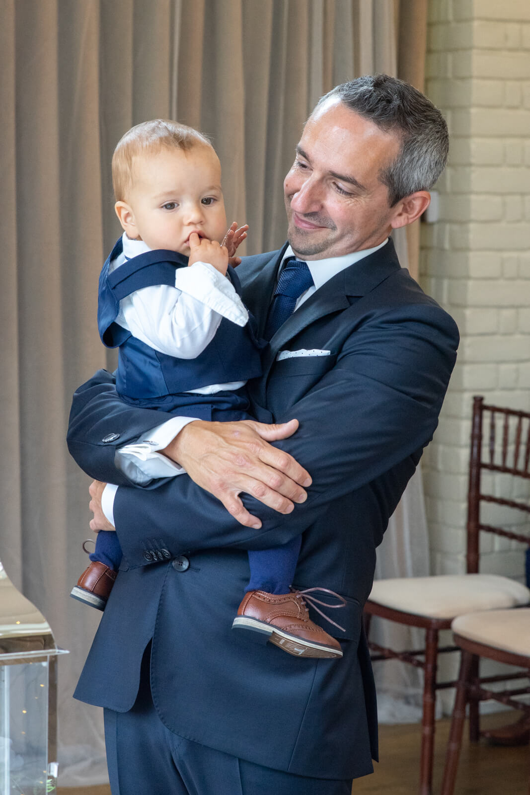Groom waiting for the bride with baby in his arms