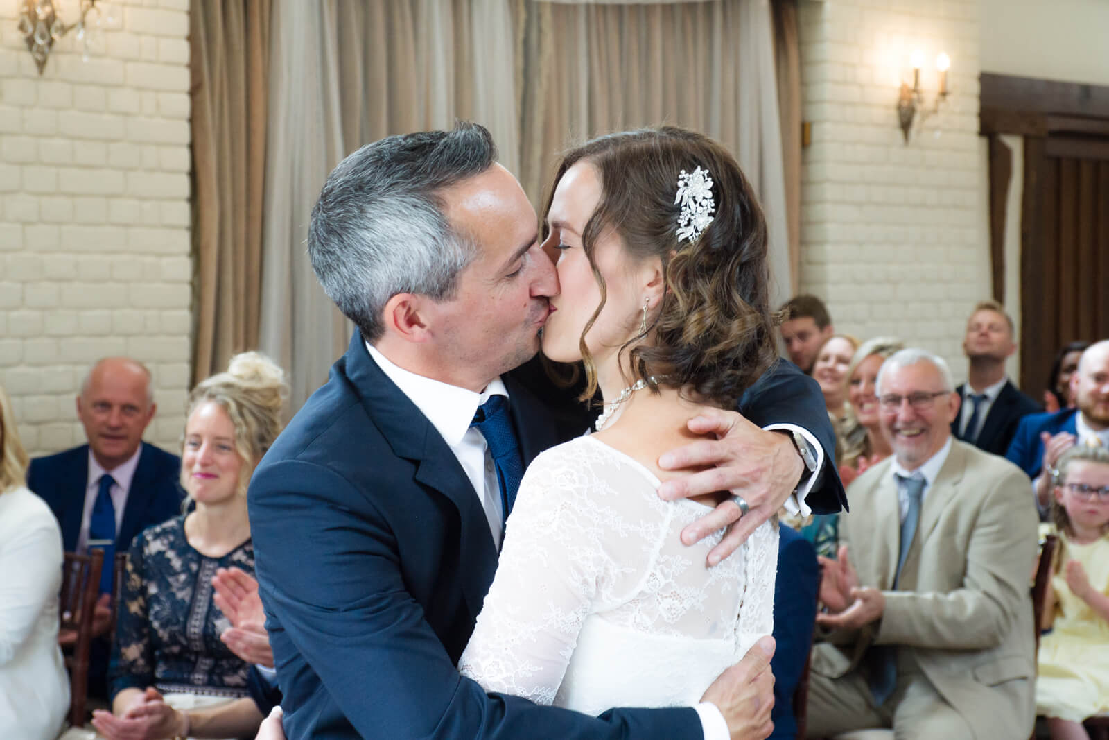 Bride and groom share a first kiss while their guests applaud