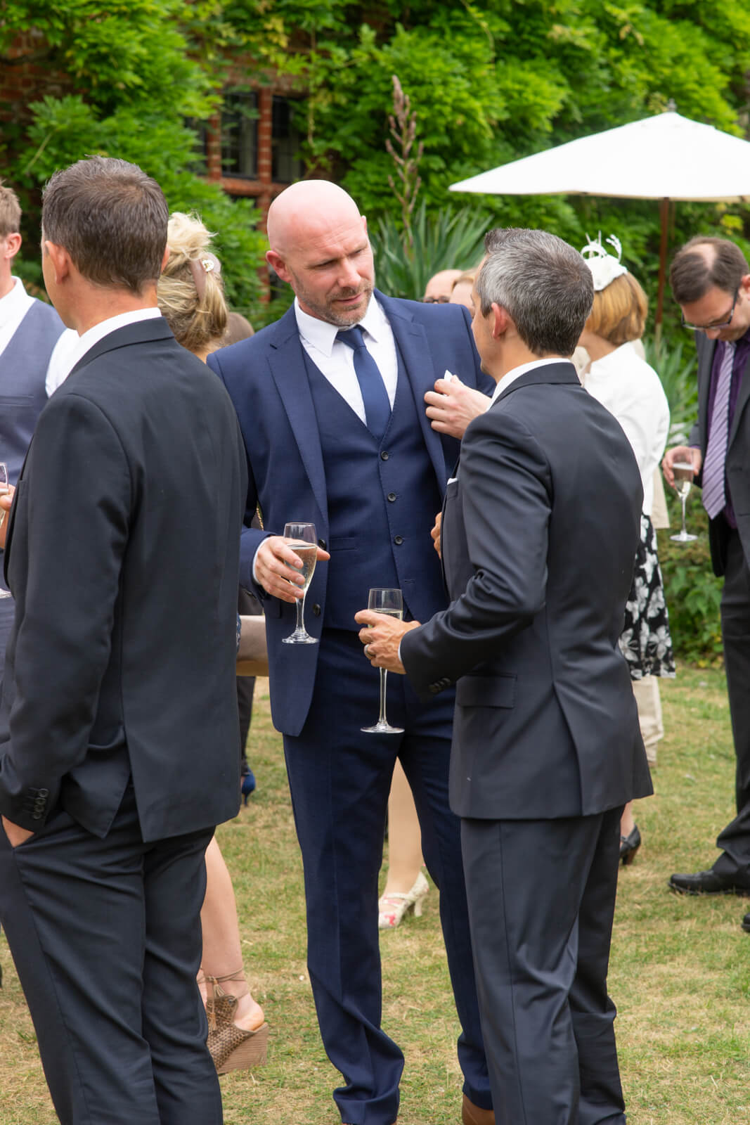 Groom and best man have a chat while drinking champagne