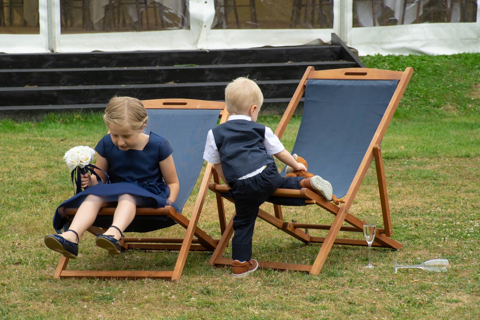 Young boy and girl in formal wear plaing on deck chairs