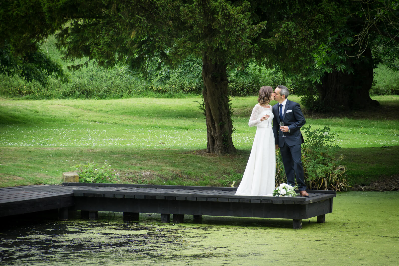 Bride and groom kiss at the end of a jetty into a green lake