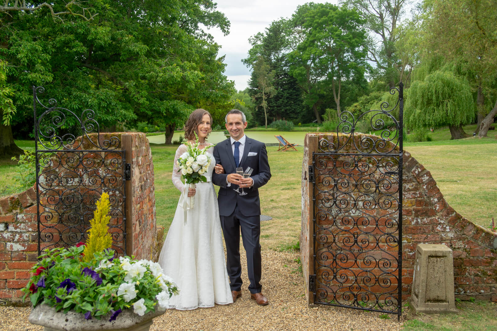 Portrait of the bride and groom standing in a redbrick and iron gateway in a country garden
