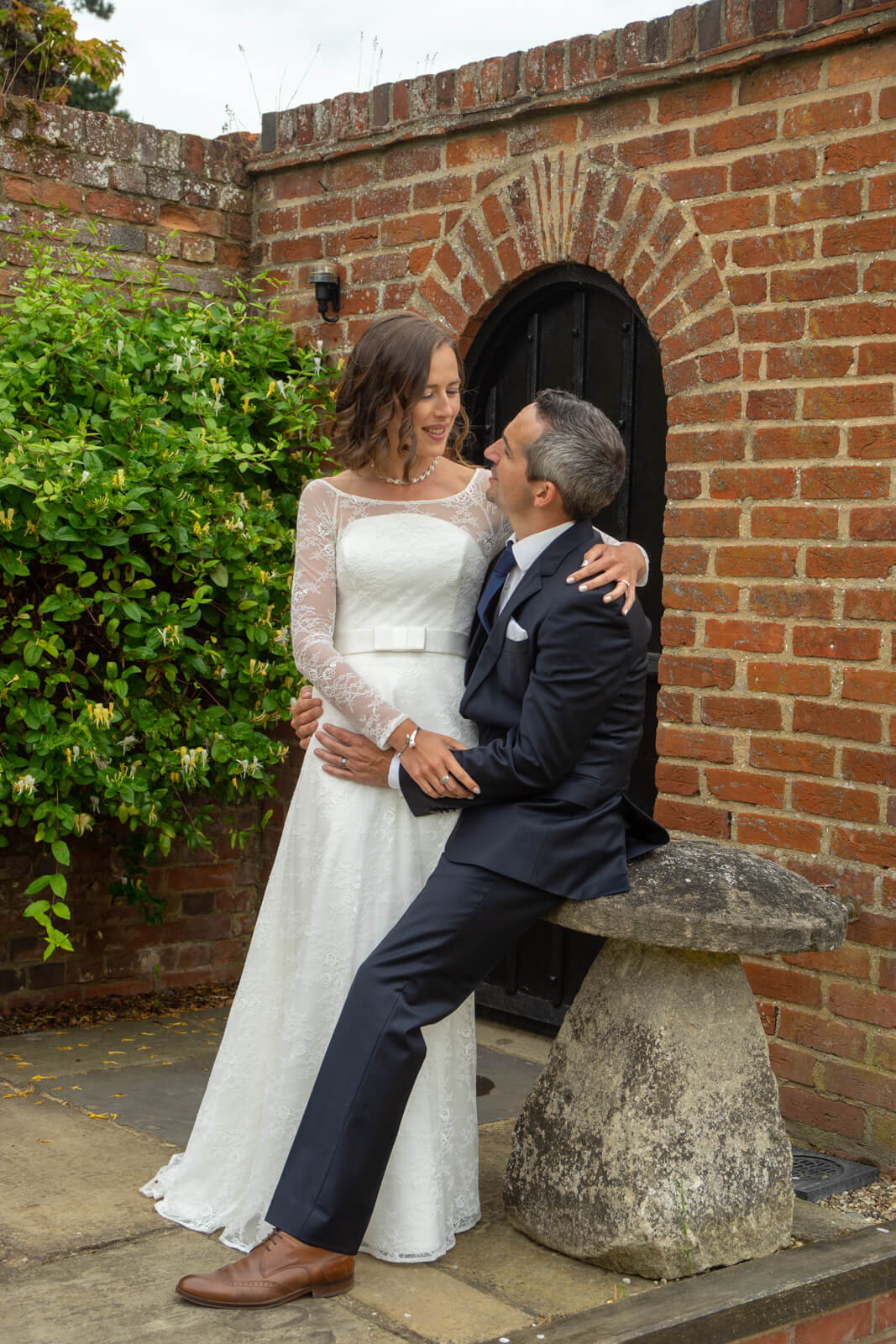 Bride sits on grooms knee against a redbrick wall