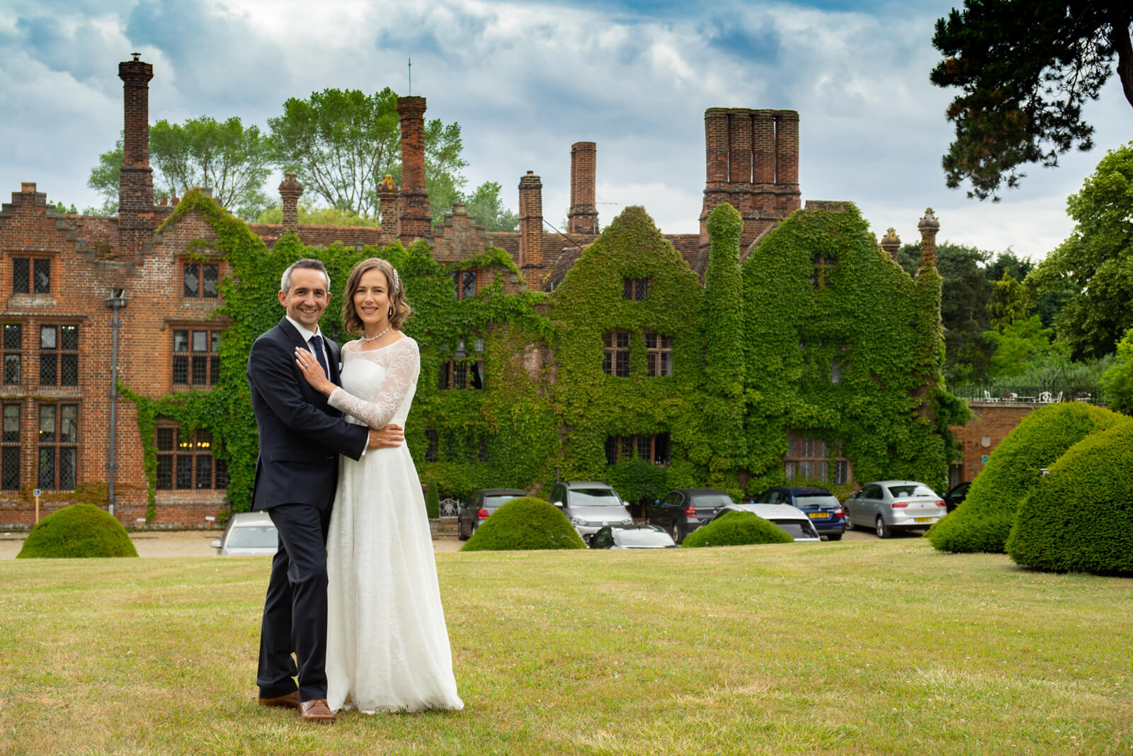 Bride and groom stand together inforn of a country manor house with tall chimneys and ivy