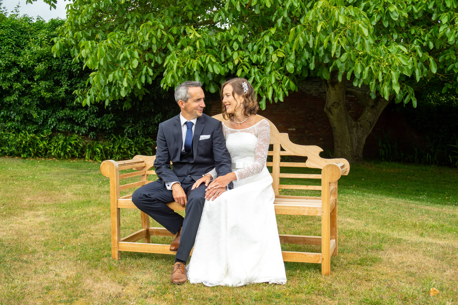 Bride and groom looking at each other and holding hands sat on a bench by a tree