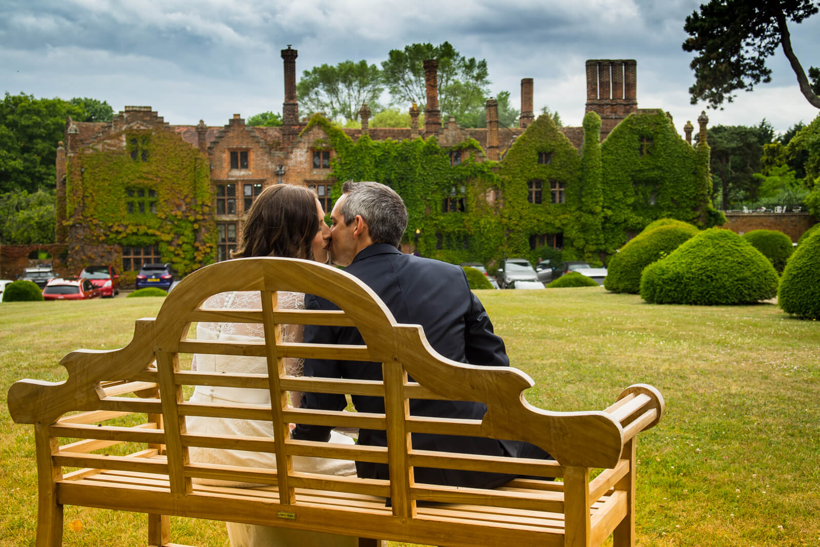 Picture of a bride and groom on a bench taken from behind with a country manor house in the background