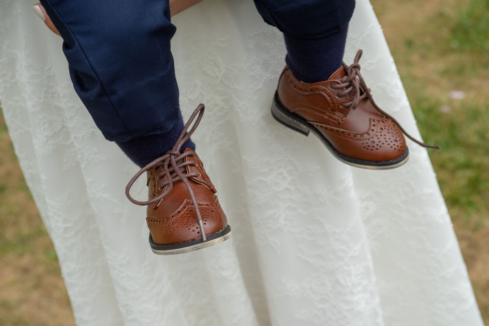 Baby's brown brogue shoes against his mum's white wedding dress