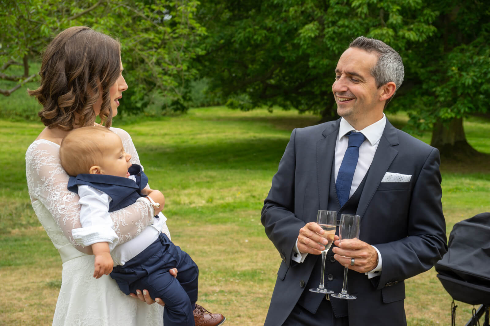 Bride and groom laugh while she holds the baby and he holds champagne