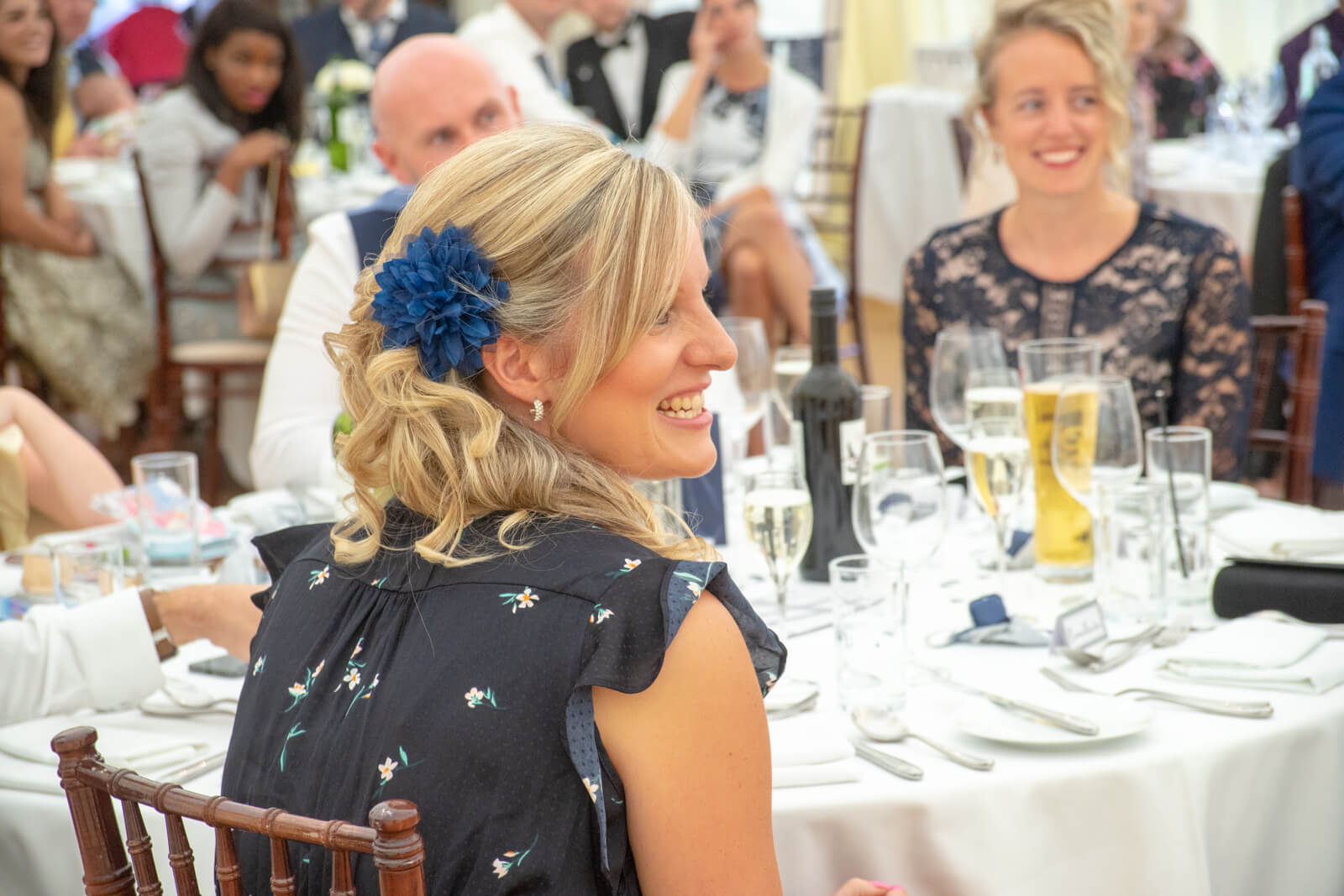 Blonde woman laughs at wedding speeches