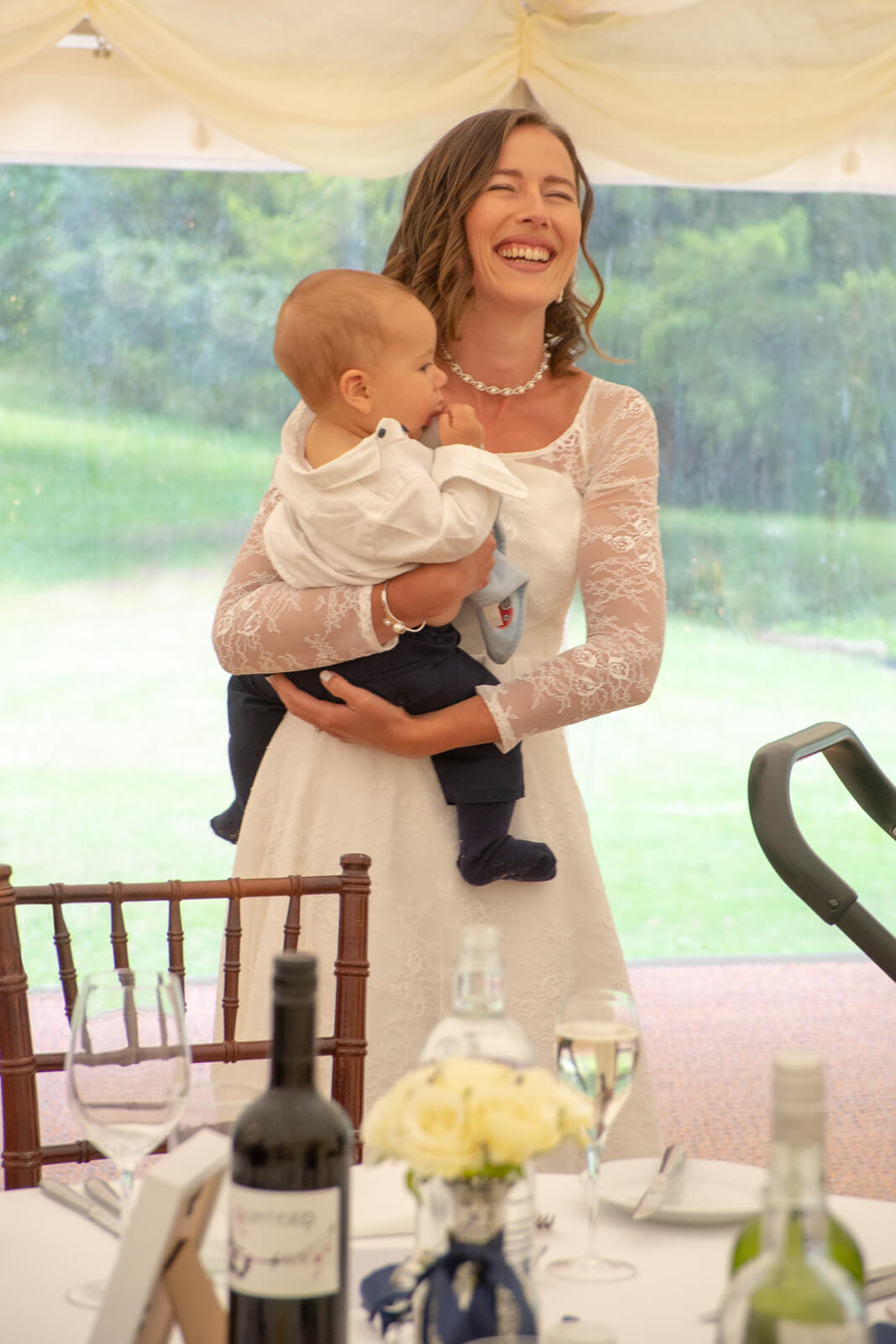 Bride holding baby laughs at wedding speeches in a marquee