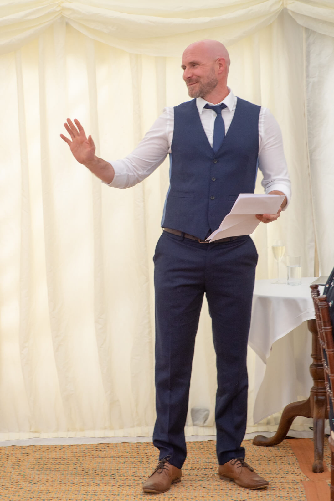 Best man laughs and holds notes whilst giving a speech