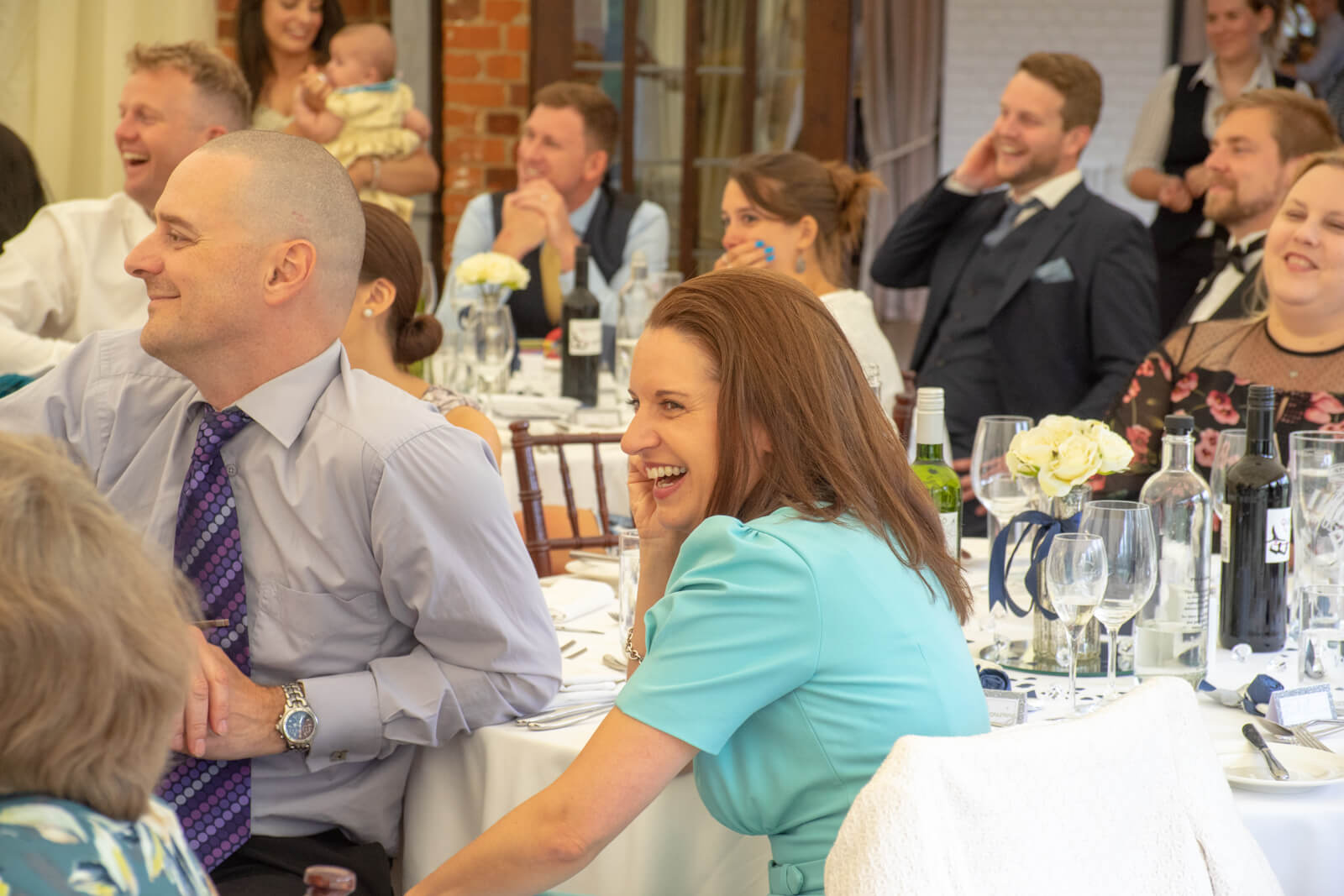 Wedding guests laughing during the speeeches at a wedding breakfast in a marquee