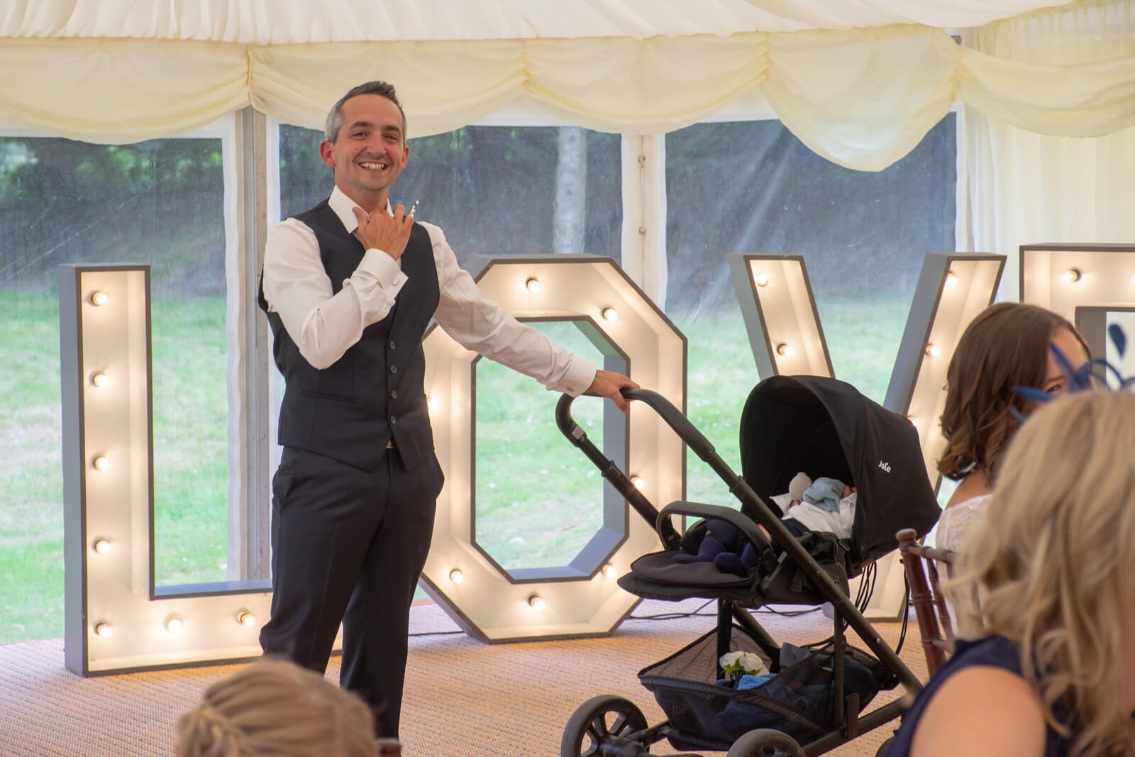 Groom loosens his collar and rocks a pram during wedding speeches