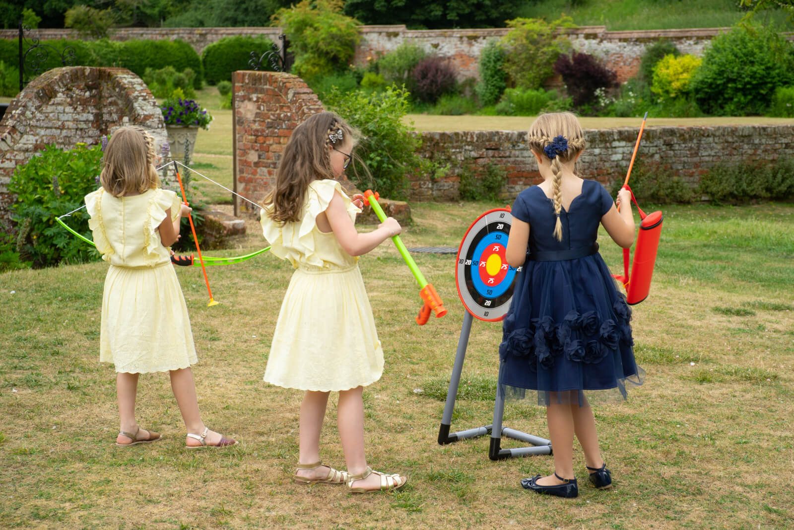 Little girls in dresses play with toys on the lawn during a wedding reception