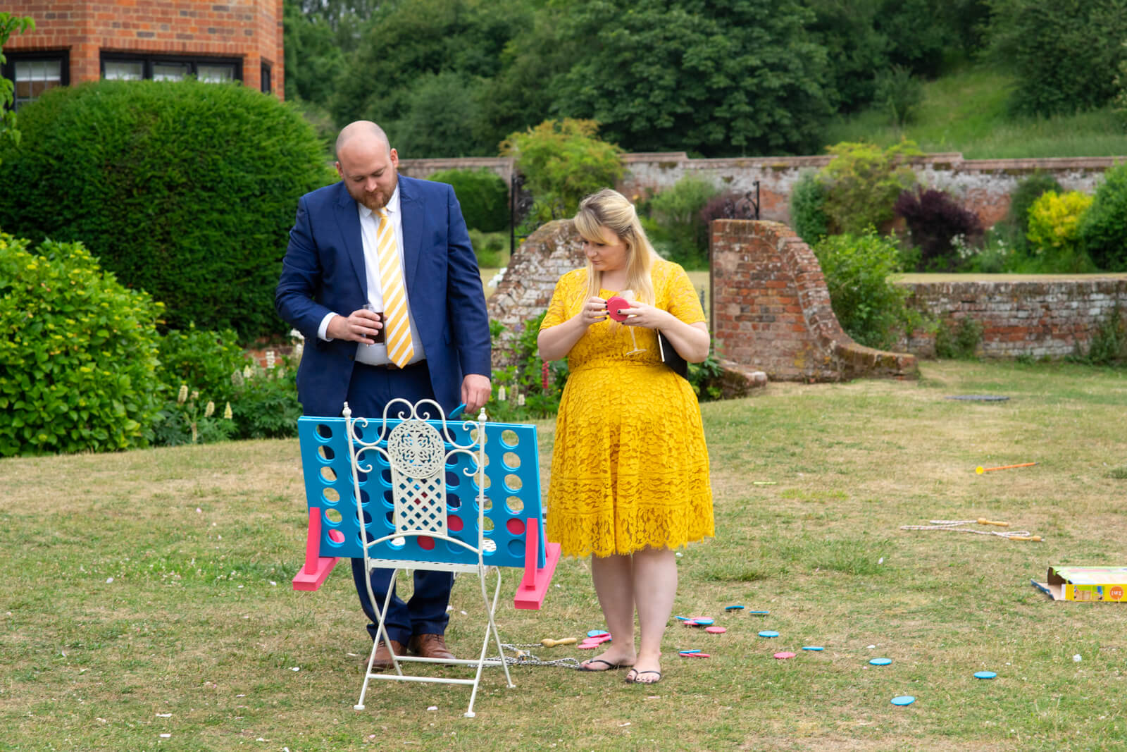 Couple at a wedding reception play giant connect four in the garden