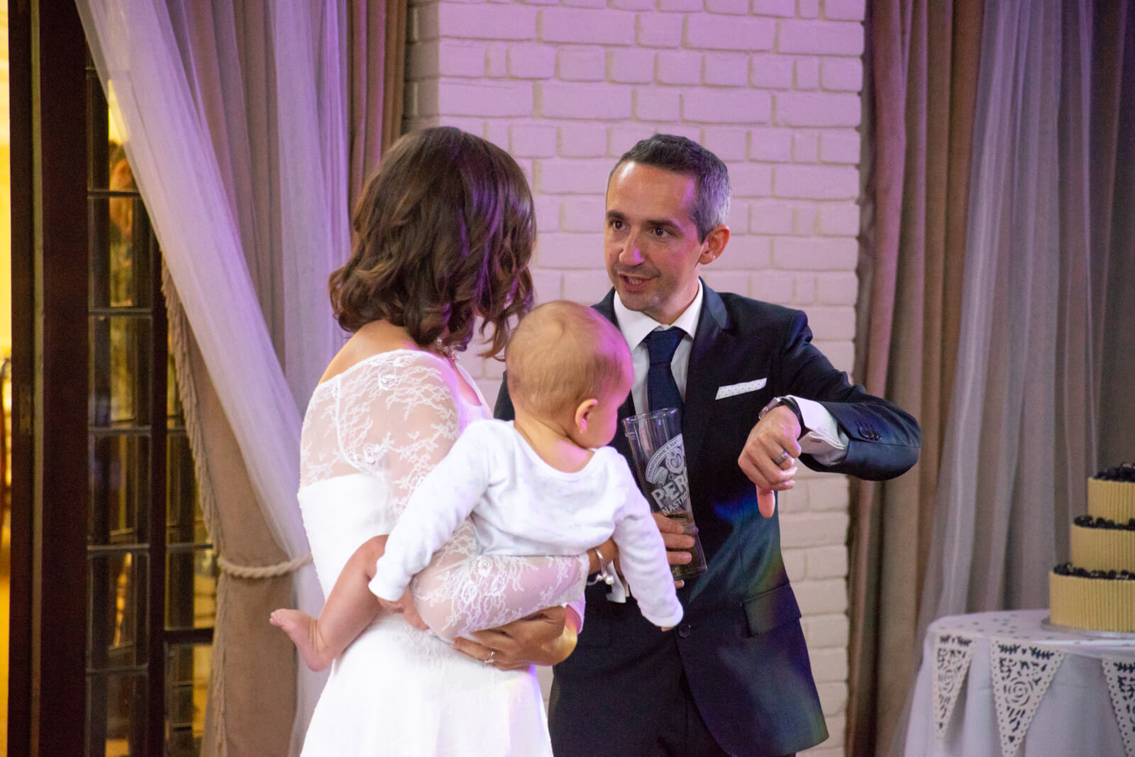 Groom looks at his watch while bride holds their baby