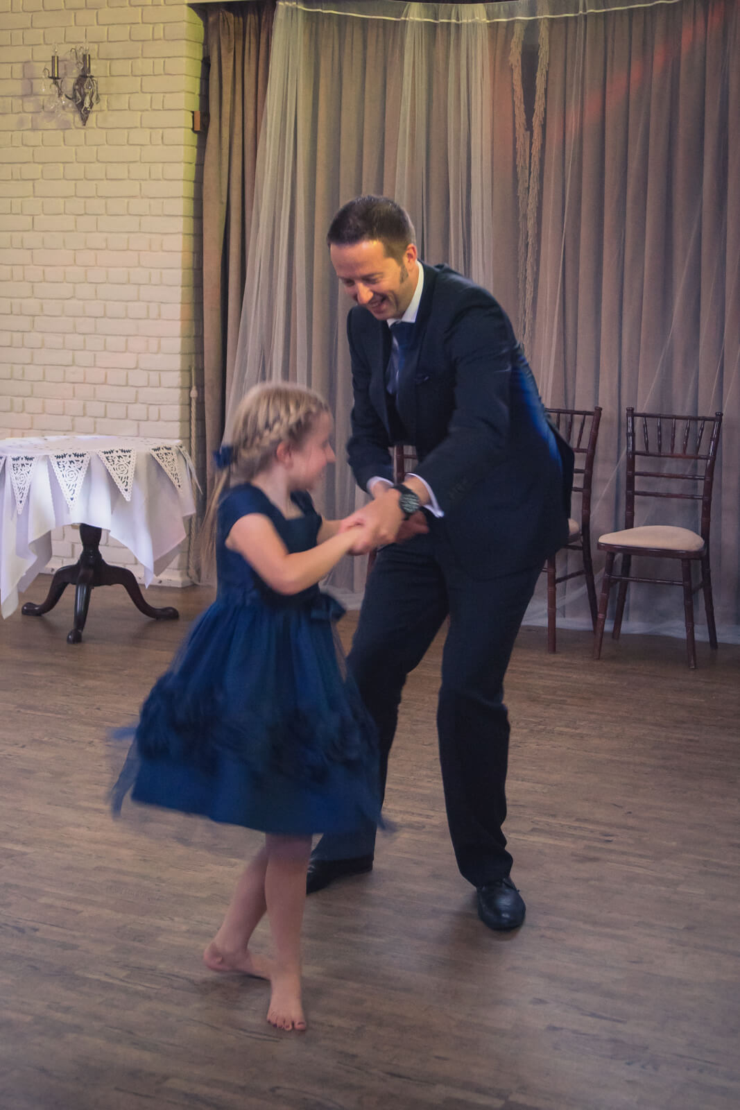 Dad and young daughter dance together at wedding reception