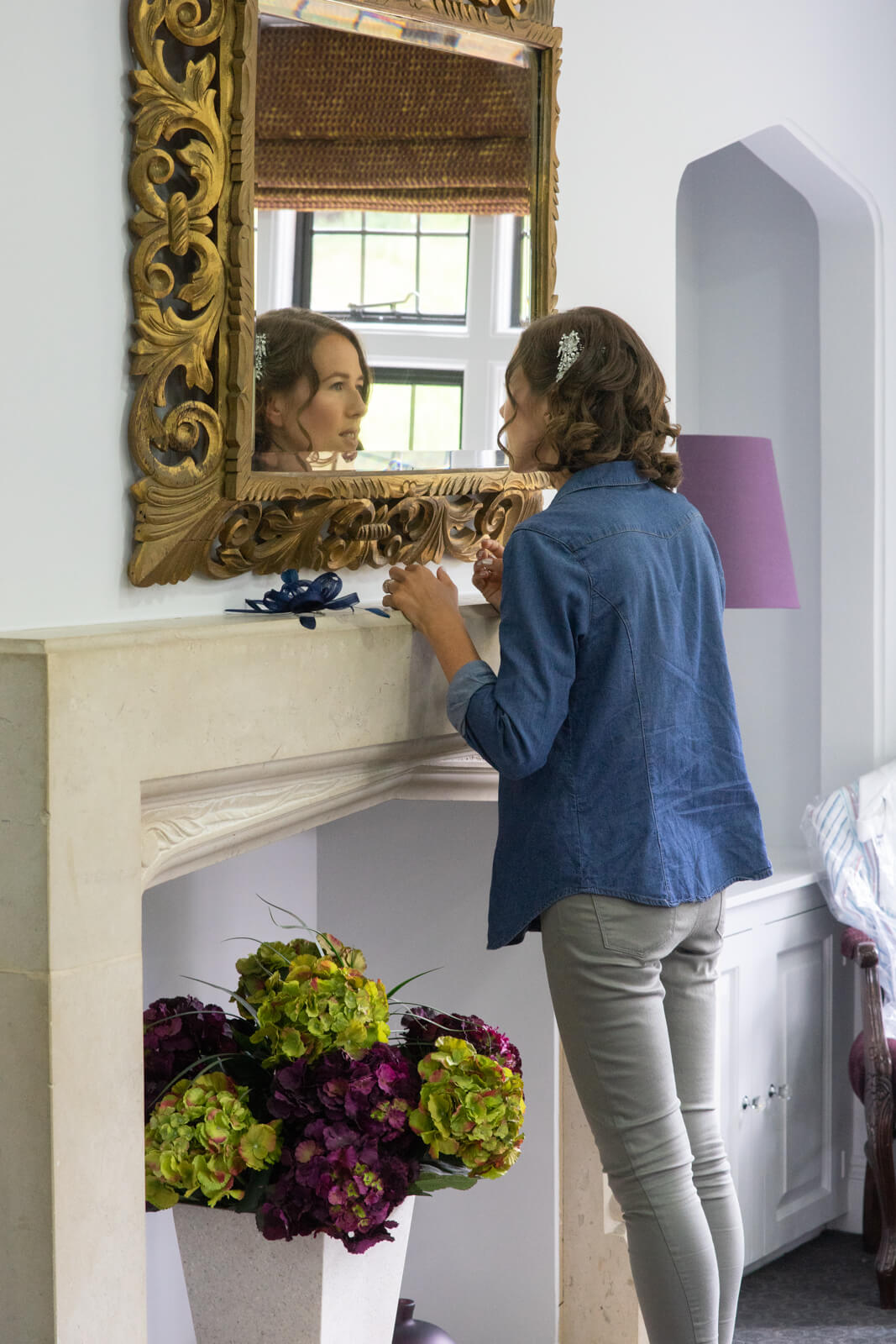 Bride to be doing her make up in a mirror over a mantlepiece