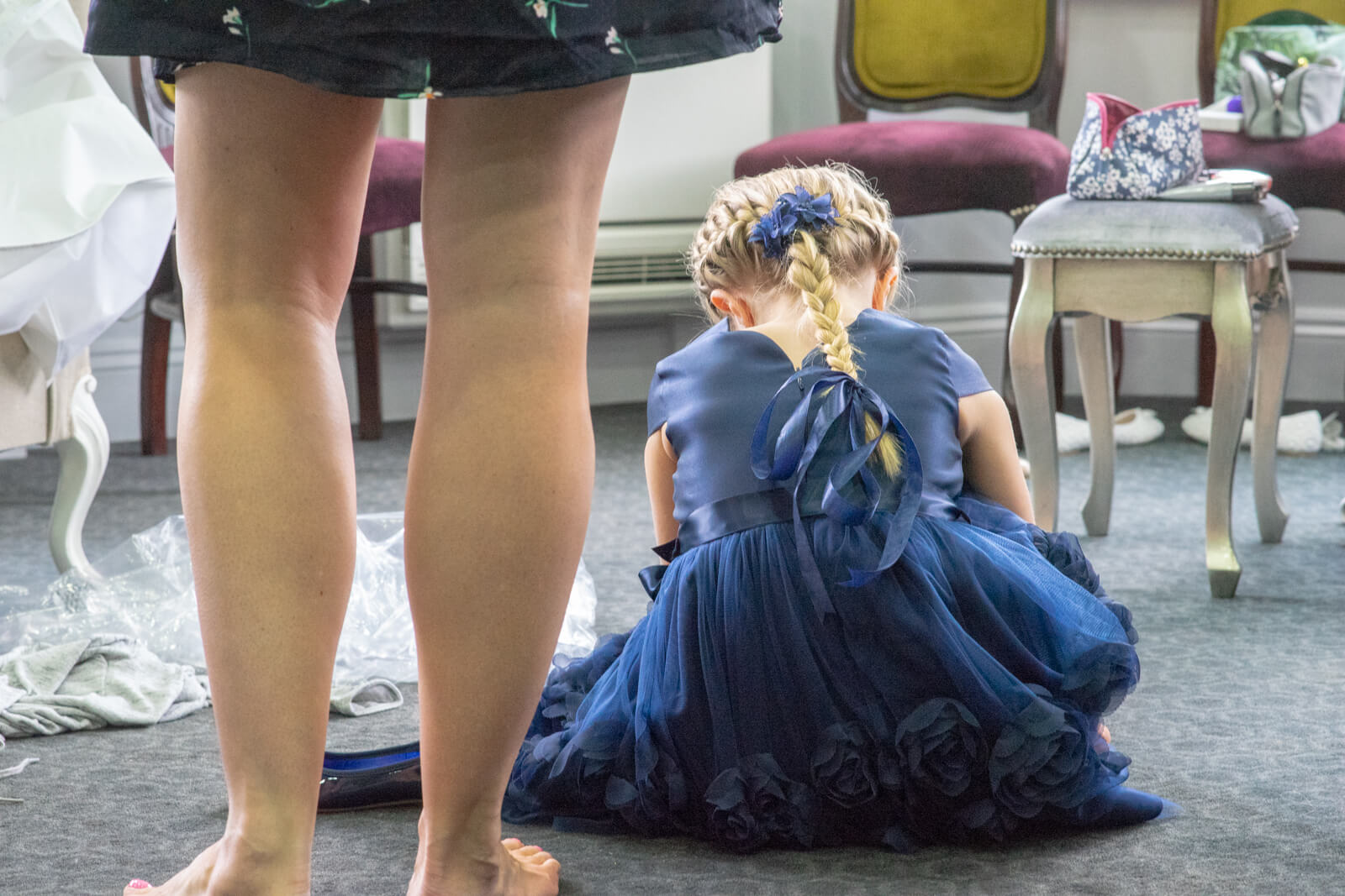 Child bridesmaid in blue dress sitting on the floor taken from behind