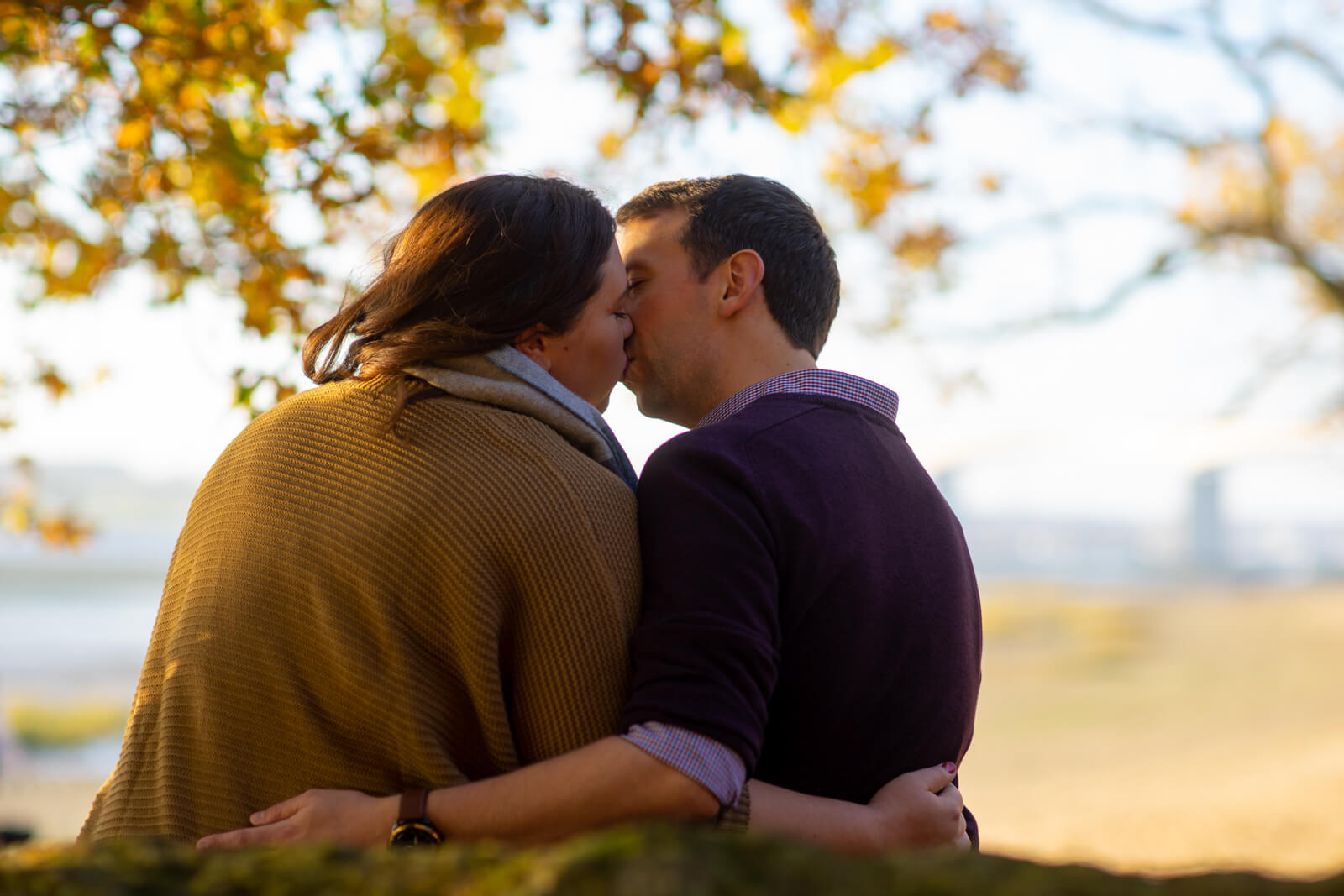 Photo of a young couple kissing taken from behind with a beach in the background.
