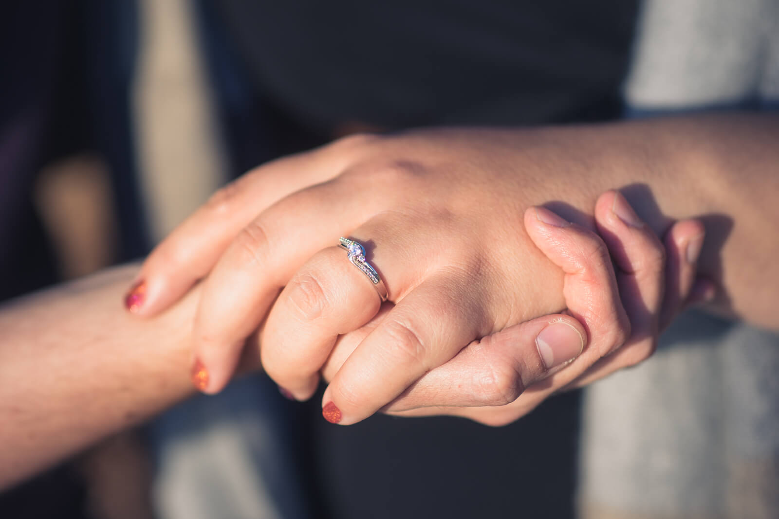 Young couple's hands with engagement ring
