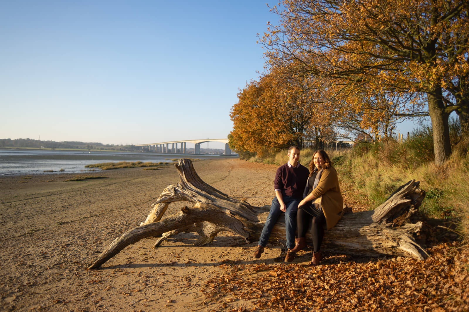 Engagement photo of a couple sitting on driftwood on an autumnal beach