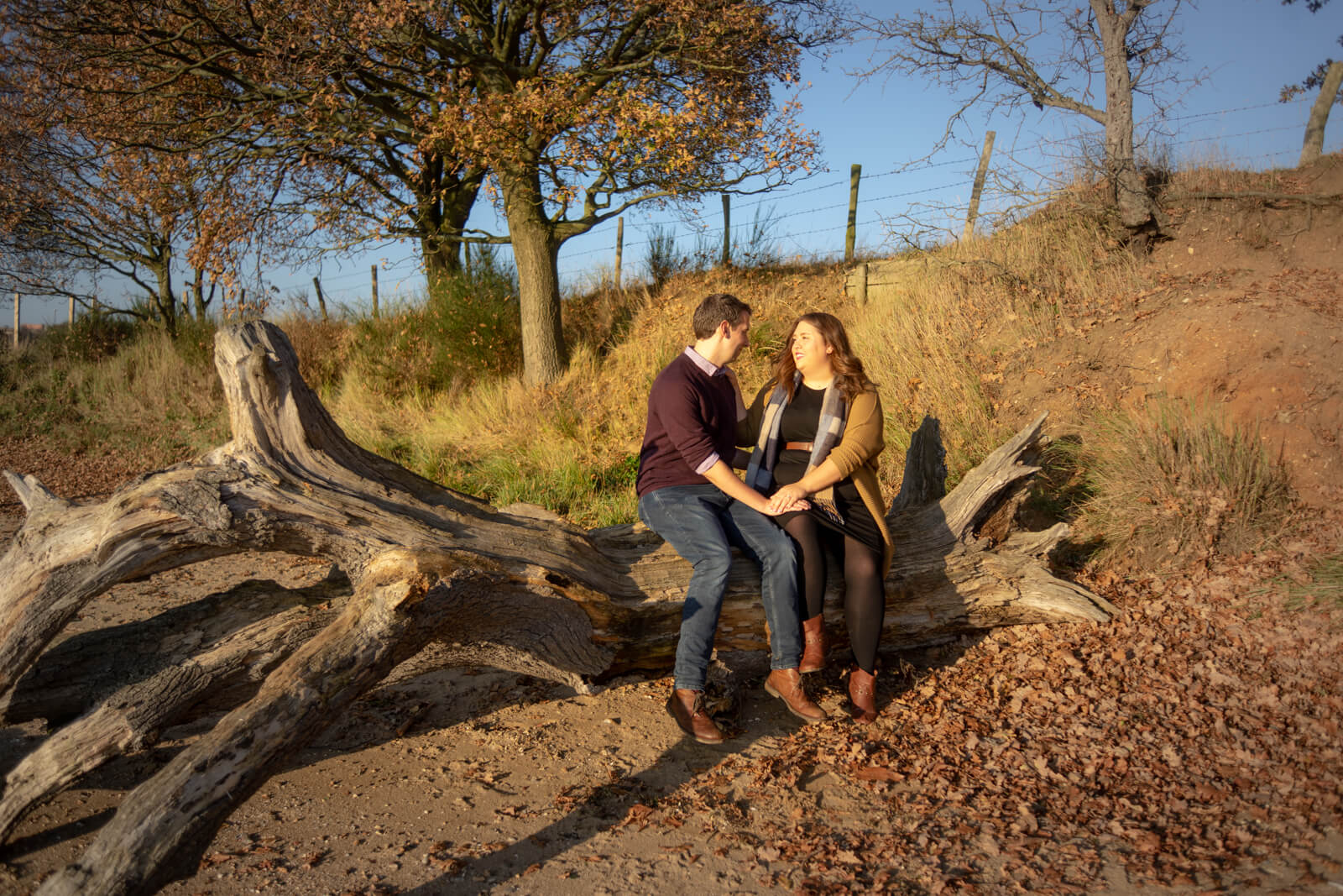 Engaged couple sitting on driftwood facing each other in evening sunshine