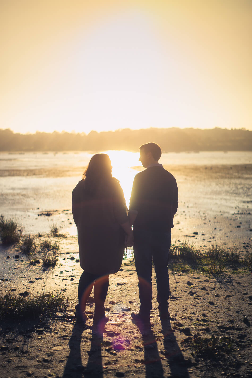 Silhouette of engaged couple holding hands and looking at the evening sun over the water