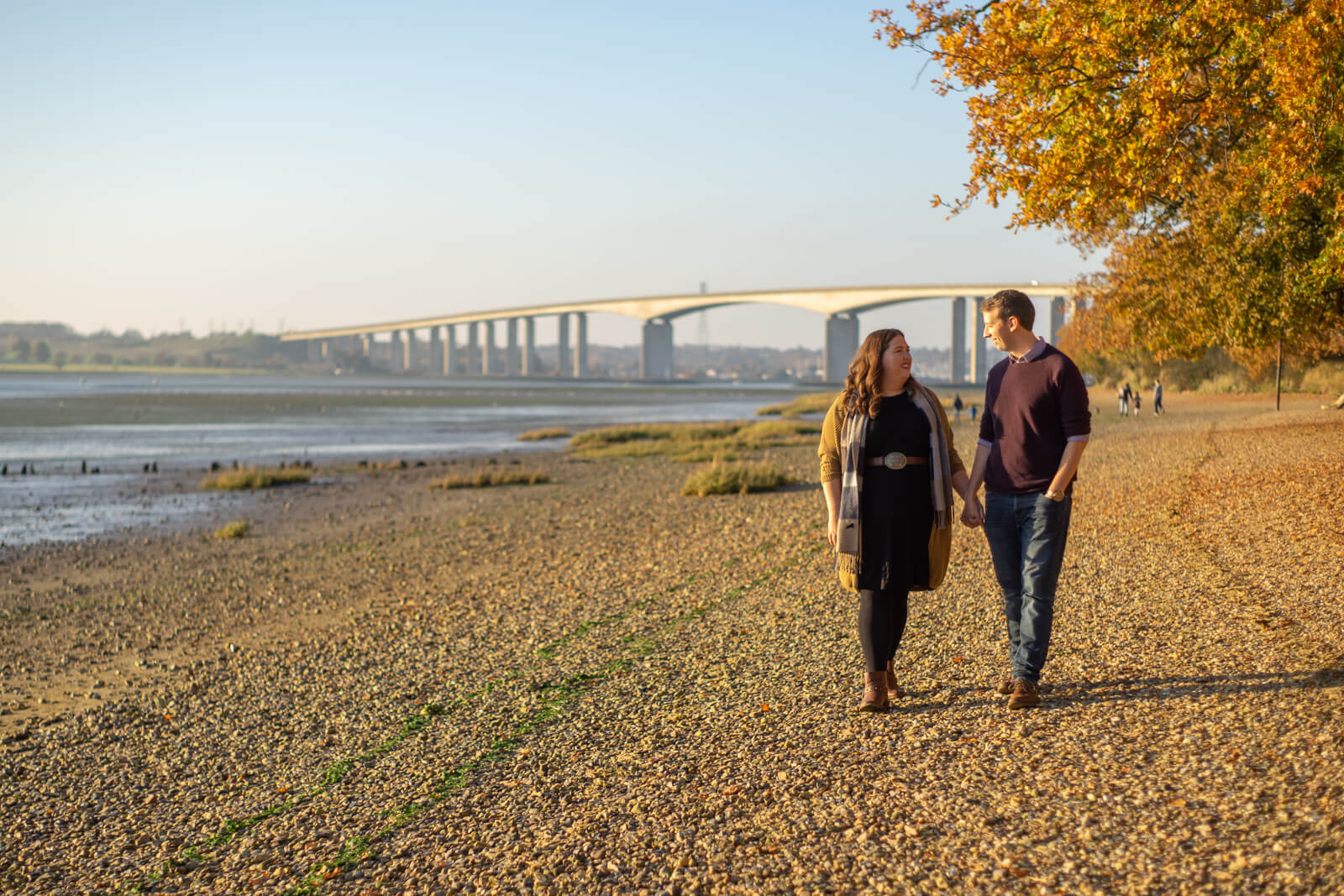 Engagement photography of a couple walking aling a shingle beach with a bridge in the background