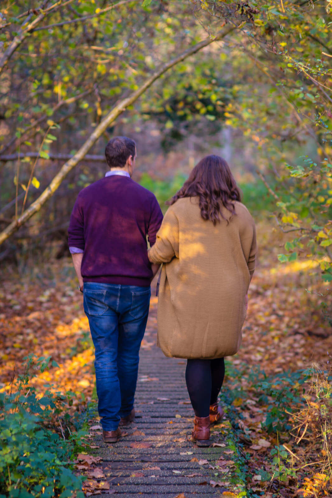 Engaged couple walking on wooden path through autumn trees