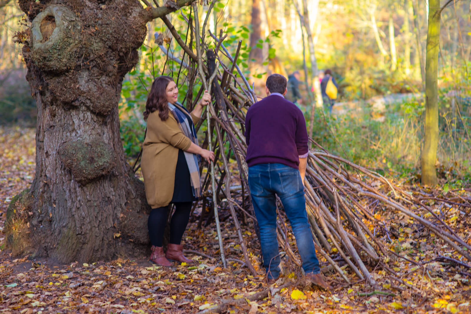 Engaged couple having fun builing a woodland den out of fallen branches